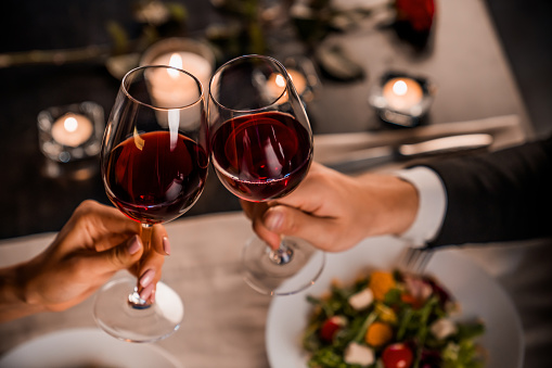 Close up of young couple toasting with glasses of red wine at restaurant 1184016689