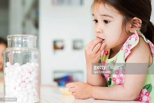 Close up of young girl tasting marshmallows