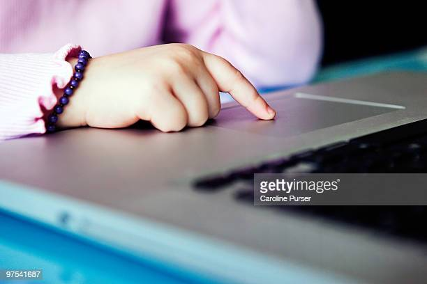 Close up of young girl's hand on laptop