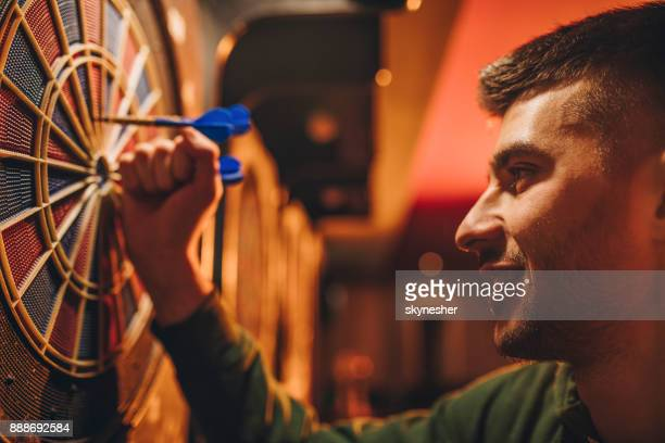 close up of young happy man taking darts out of dart board. - dart stock pictures, royalty-free photos & images
