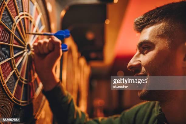close up van jonge gelukkig man darten van dart bord op te nemen. - darts stockfoto's en -beelden