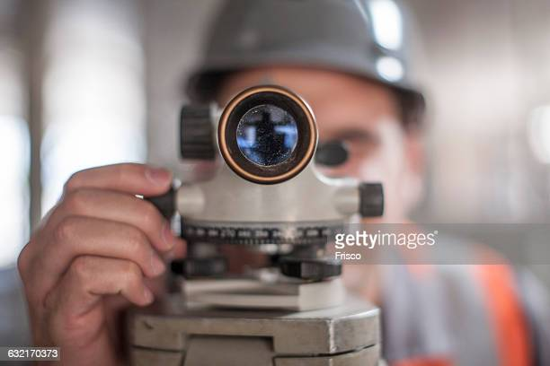 close up of young male surveyor looking through theodolite on construction site - surveyor stock photos and pictures