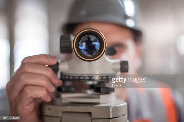 close up of young male surveyor looking through theodolite on construction site - inspetora - fotografias e filmes do acervo