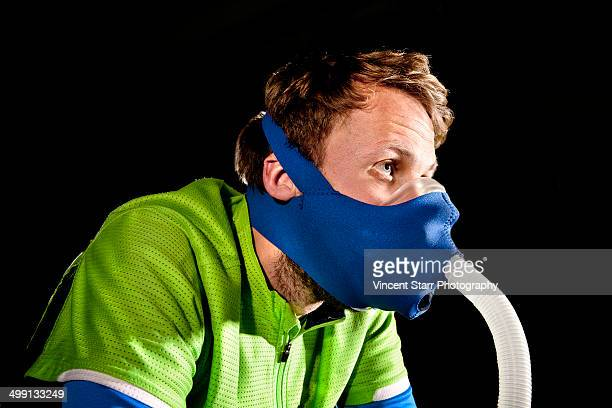 Close up of young man in face mask on gym exercise cycle in altitude centre