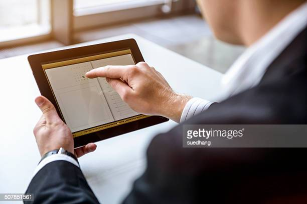 Close up of young man in office using touchscreen on digital tablet