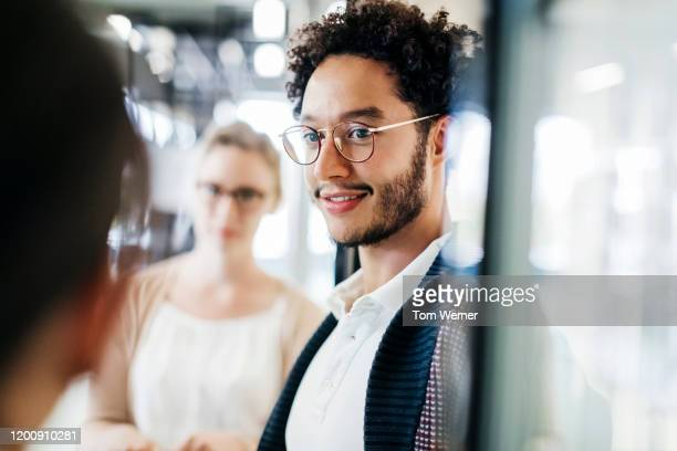 close up of young man talking to colleague in public library - studenten stock-fotos und bilder