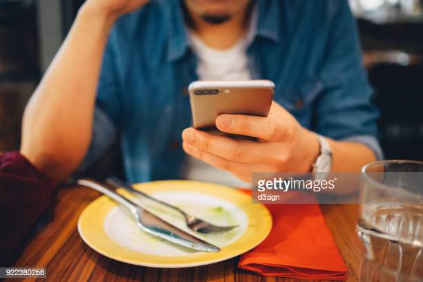 Close up of young man using mobile phone while having meal in a restaurant
