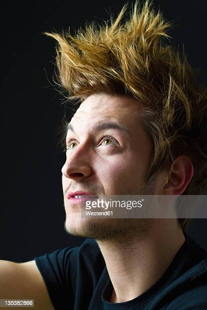 Close up of young man with spiky hair against black background, looking up
