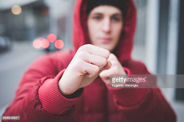 close up of young mans posing with clenched fists on city street - combat sport stock pictures, royalty-free photos & images