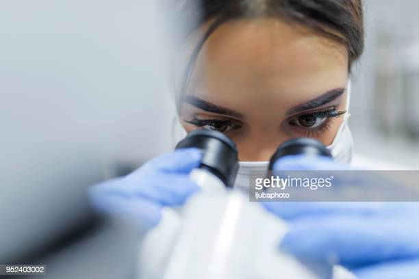 close up of young scientist looking through a microscope in a laboratory - microscope stock pictures, royalty-free photos & images
