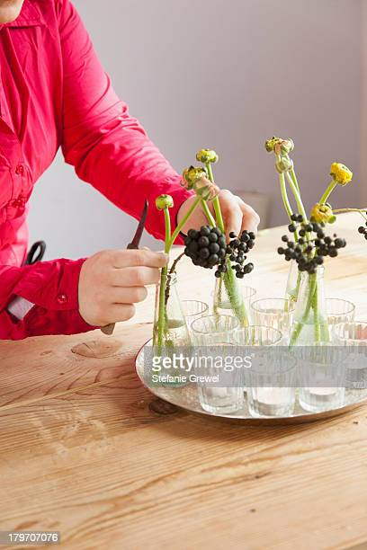 Close up of young woman arranging fresh flowers and plants