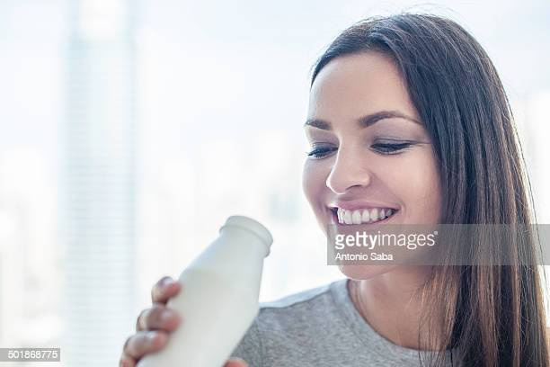 Close up of young woman drinking milk