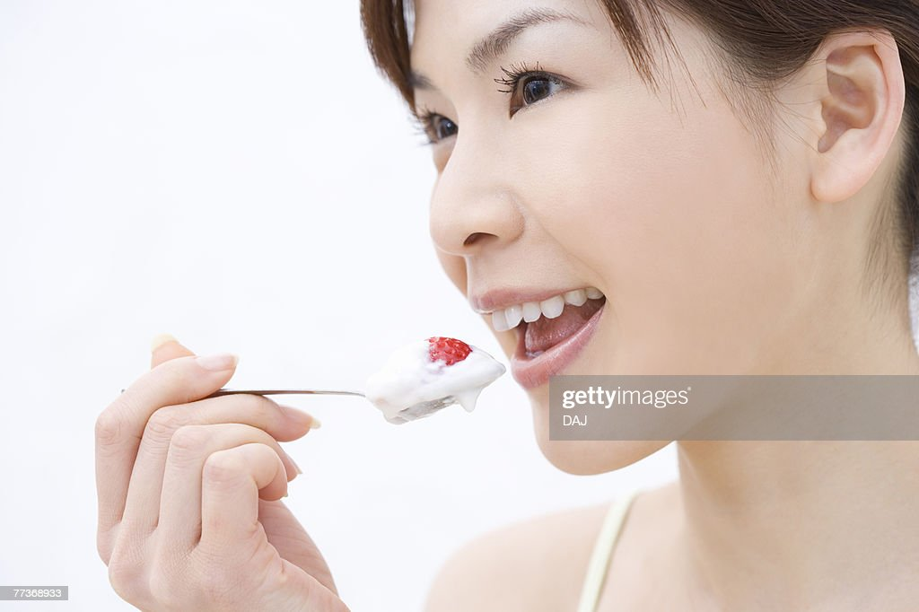 Close up of young woman eating a strawberry, side view : Foto de stock