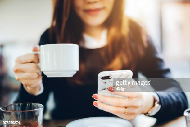 close up of young woman having coffee and reading news on mobile phone in the early morning before work - 週末の予定 ストックフォトと画像