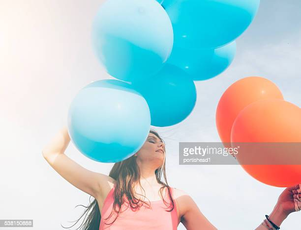 Nahaufnahme einer jungen Frau halten Haufen bunte Ballons
