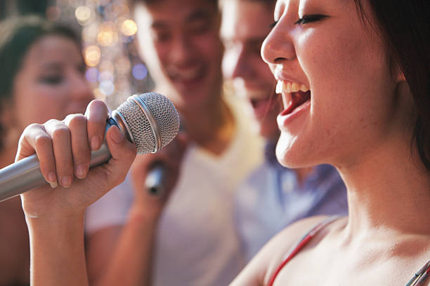 close- up of young woman holding a microphone and singing at karaoke, friends singing in the background - a hand holding a microphone stock pictures, royalty-free photos & images