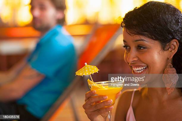 Close up of young woman holding cocktail at indoor beach party