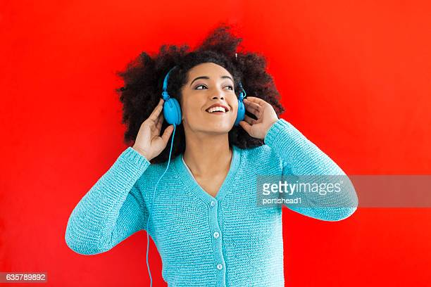Close up of young woman listening music on red background