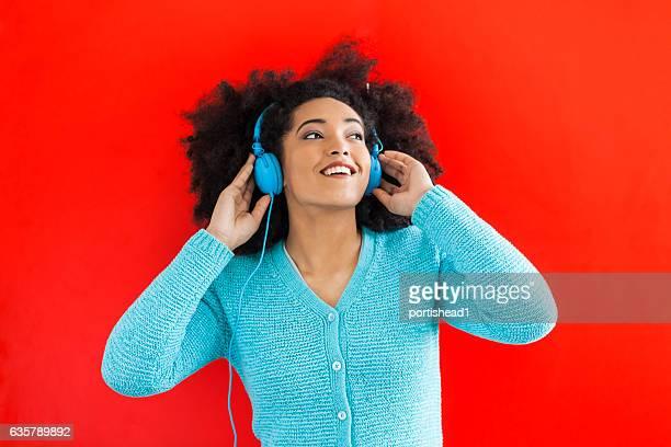 Gros plan de jeune femme écoutant de la musique sur fond rouge