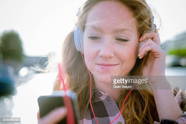 Close up of young woman listening to music on headphones on street