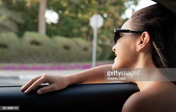 Close up of young woman looking out of taxi window