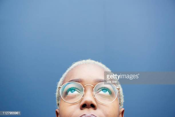close up of young woman looking up. - looking up stock pictures, royalty-free photos & images