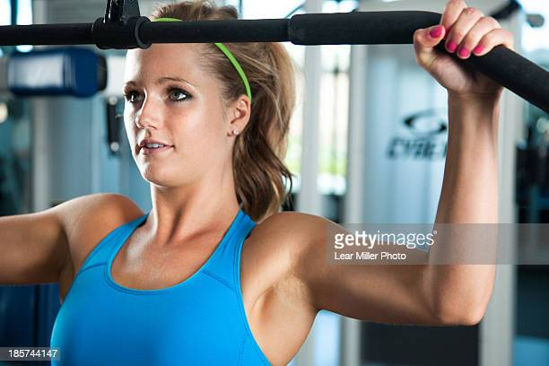 Close up of young woman pulling weights