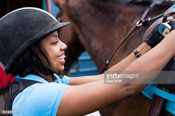 close up of young woman putting saddle on horse - riding hat stock pictures, royalty-free photos & images