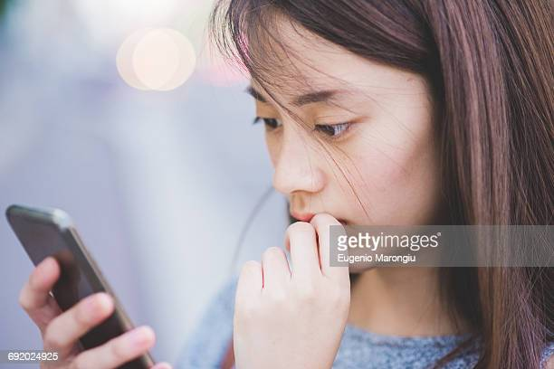 close up of young woman reading smartphone - 見つめる ストックフォトと画像