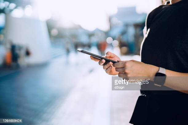 close up of young woman typing on smartphone while commuting in the city against beautiful sunlight. she is also wearing a smartwatch. business on the go concept - スマートウォッチ ストックフォトと画像