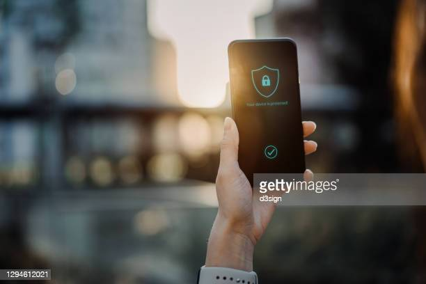 close up of young woman using smartphone in downtown district in the city against urban city scene, with a security key lock icon on the smartphone screen. privacy protection, internet and mobile security concept - 防犯システム ストックフォトと画像