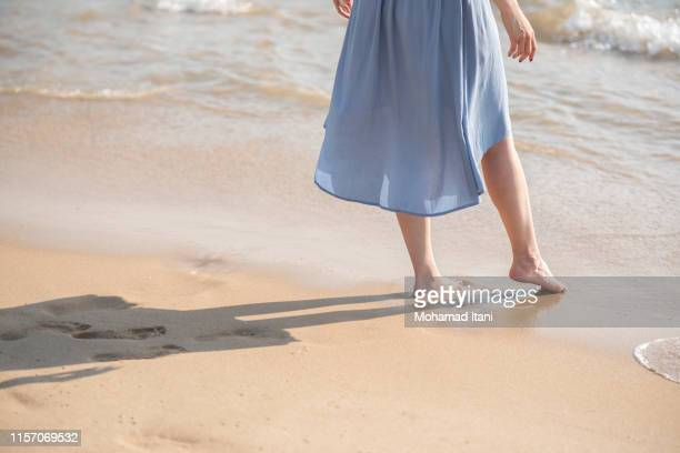 close up of young woman wading on the seashore - arab feet photos et images de collection