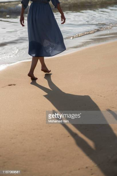 close  up of young woman walking on the seashore - arab feet photos et images de collection