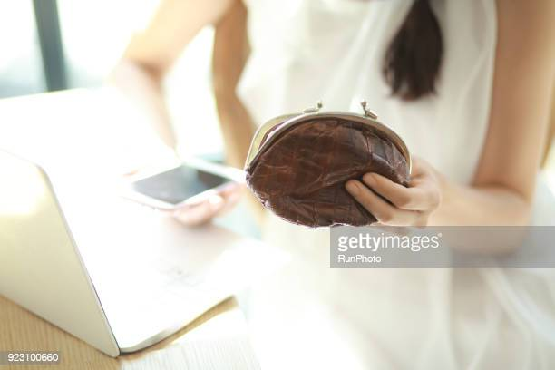 Close up of young woman with change purse in cafe