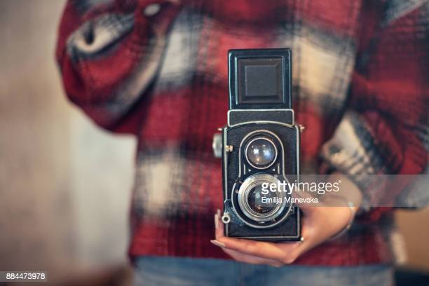 Close up of young woman with vintage camera