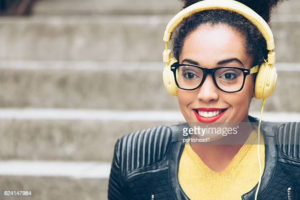 Close up of young woman with yellow headphones