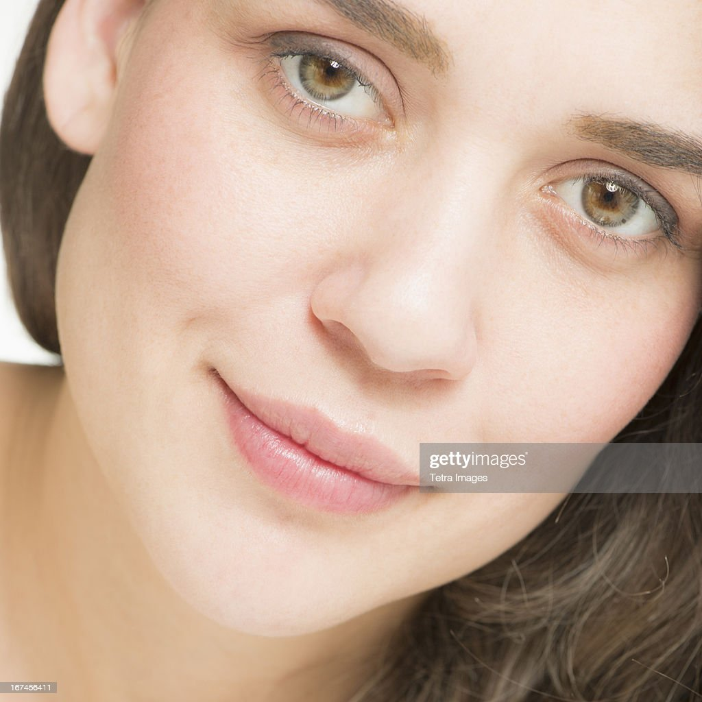 Close up of young woman's face, studio shot : Stock Photo