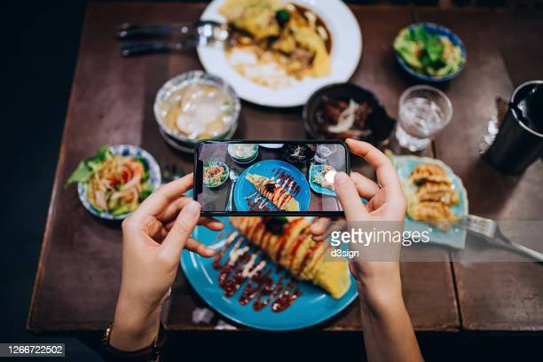 close up of young woman's hand taking photo of freshly served traditional japanese omurice (stir-fried rice wrapped in an omelet), with miso soup and assorted appetitzers before eating it with smartphone in a japanese restaurant - yōshoku photos et images de collection