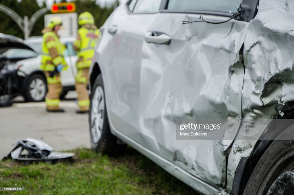 Close up on a car crashed with fireman in background : Stock Photo