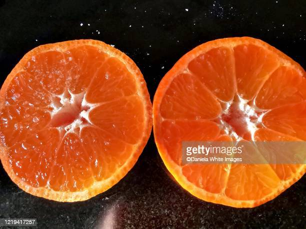 close up on a halved tangerine - succulent stock pictures, royalty-free photos & images