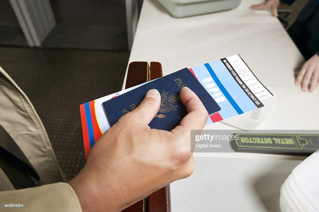 Close Up on a Man's Hand Holding a Passport and Airline Ticket : Stock Photo