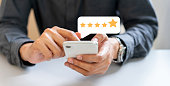 close up on businessman hand pressing on smartphone screen with gold five star rating feedback icon and press level excellent rank for giving best score point to review the service , technology business concept