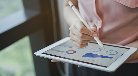 close up on businesswoman manager hand using stylus pen for writing or comment on screen dashboard tablet in meeting situation about company's performance , technology and business strategy concept 1097297162