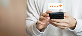 close up on customer man hand pressing on smartphone screen with gold five star rating feedback icon and press level excellent rank for giving best score point to review the service , technology business concept