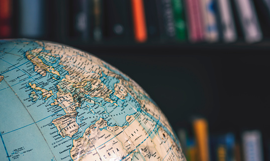 Close up on desktop globe. Europe and Northern Africa. In background out of focus books on shelves 1131195197