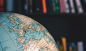Close up on desktop globe. Europe and Northern Africa. In background out of focus books on shelves