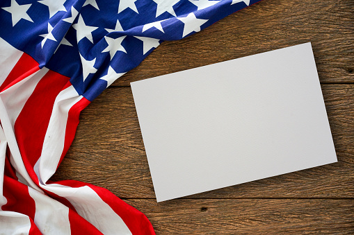 close up on mock up white paper texture with vintage crumpled retro of America flag on wood table top background for design concept 1129335895