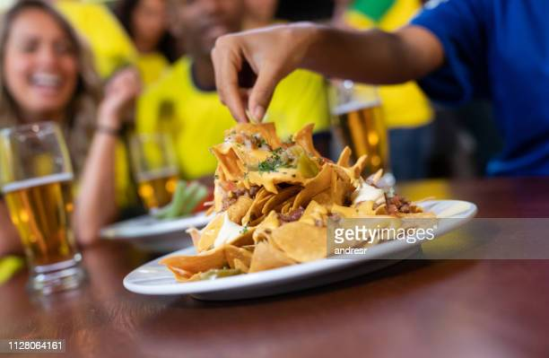 close up on nachos at a sports bar - nachos stock photos and pictures