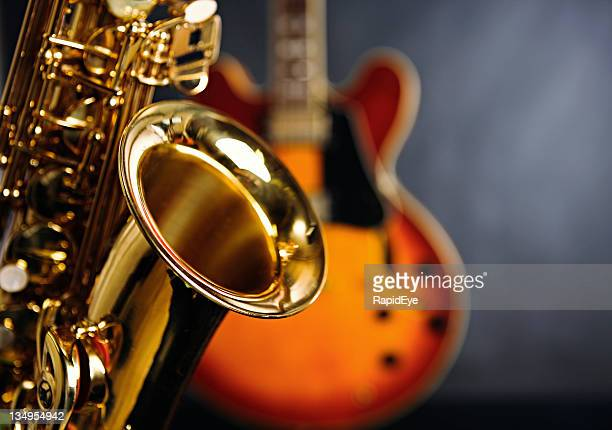 close up on saxophone with guitar in background. jazz rules! - saxophone stock pictures, royalty-free photos & images