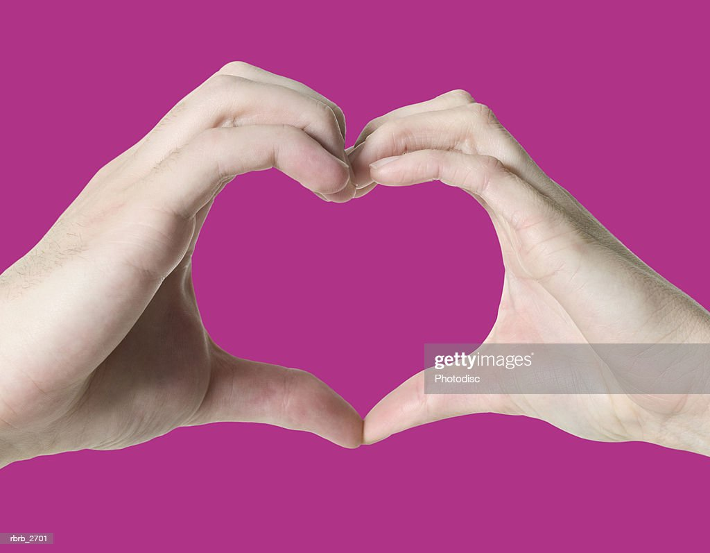 close up on the hands of a woman as she makes the shape of a heart with her fingers : Foto de stock